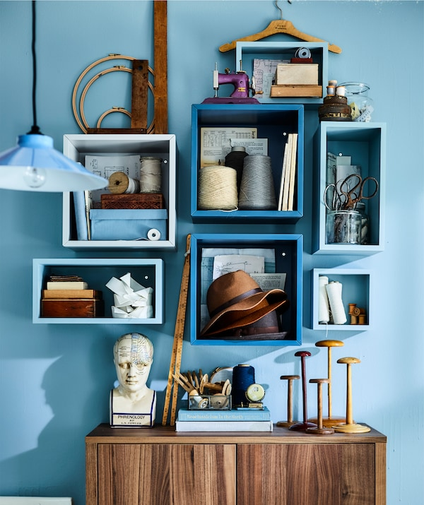 Sewing equipment and books stored in white cubed units on a blue wall.