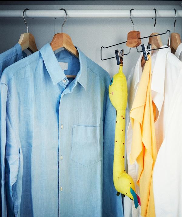 صف من القمصان معلقة على عمود خزانة ملابس. واحدة من الشماعات عليها بدلاً عن ذلك دمية ناعمة وبطانية مثبّتة عليها.