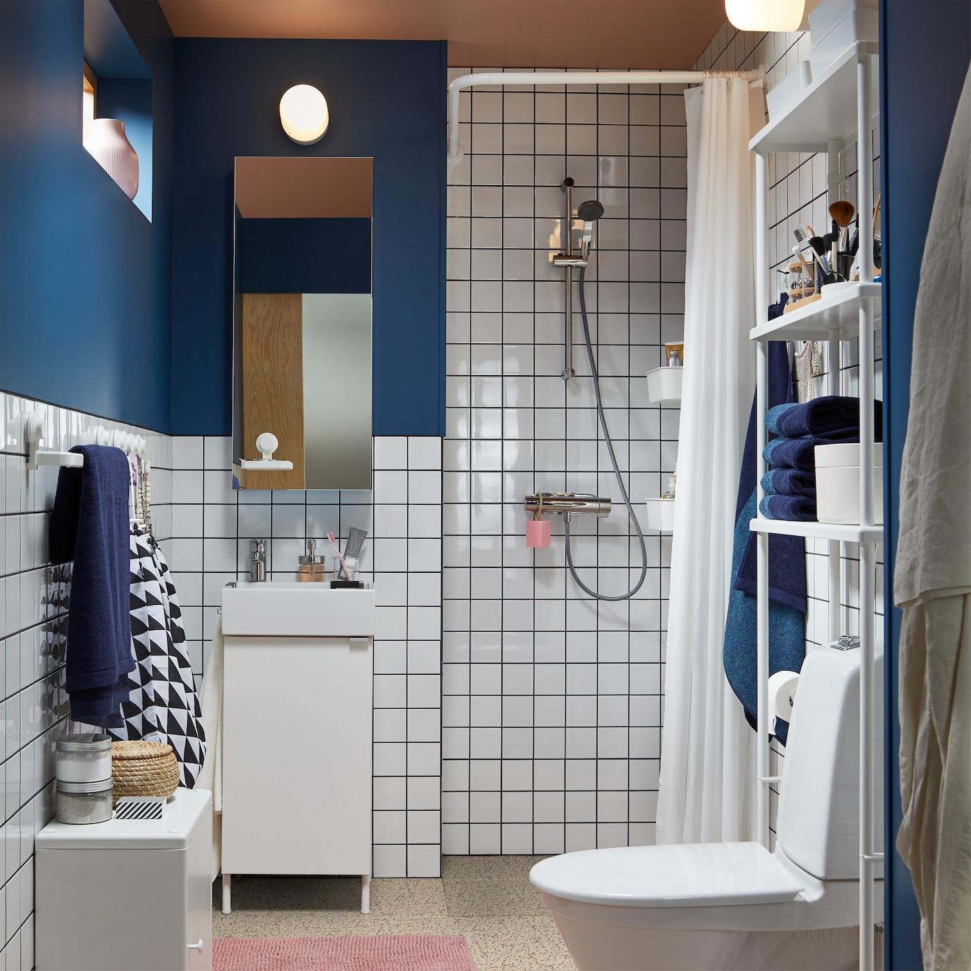 シャワー、ホワイトの家具、ホワイトのタイル、ダークブルーの壁、ピンクのバスマット、ミラーキャビネット、ブルーのタオルがある小さなバスルーム。