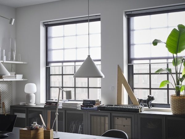 Sheer roller blinds that cover half of two windows, grey cabinets with mesh doors, a white pendant lamp and a green plant.