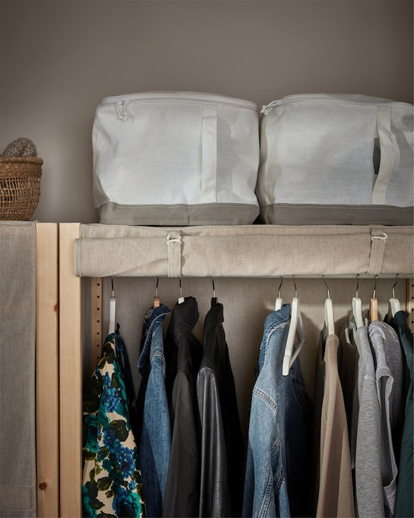 Shelving unit in pine with a rolled up cover in beige. A rail with clothes on hangers inside and white storage cases on top.
