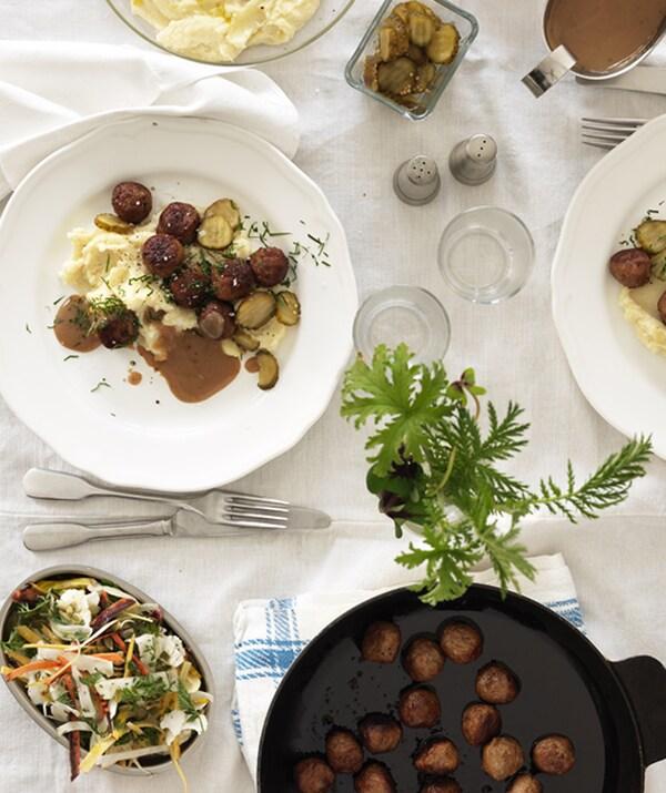 Шикарно оформленный стол с белой скатертью и двумя тарелками фрикаделек с картофельным пюре и салатом.