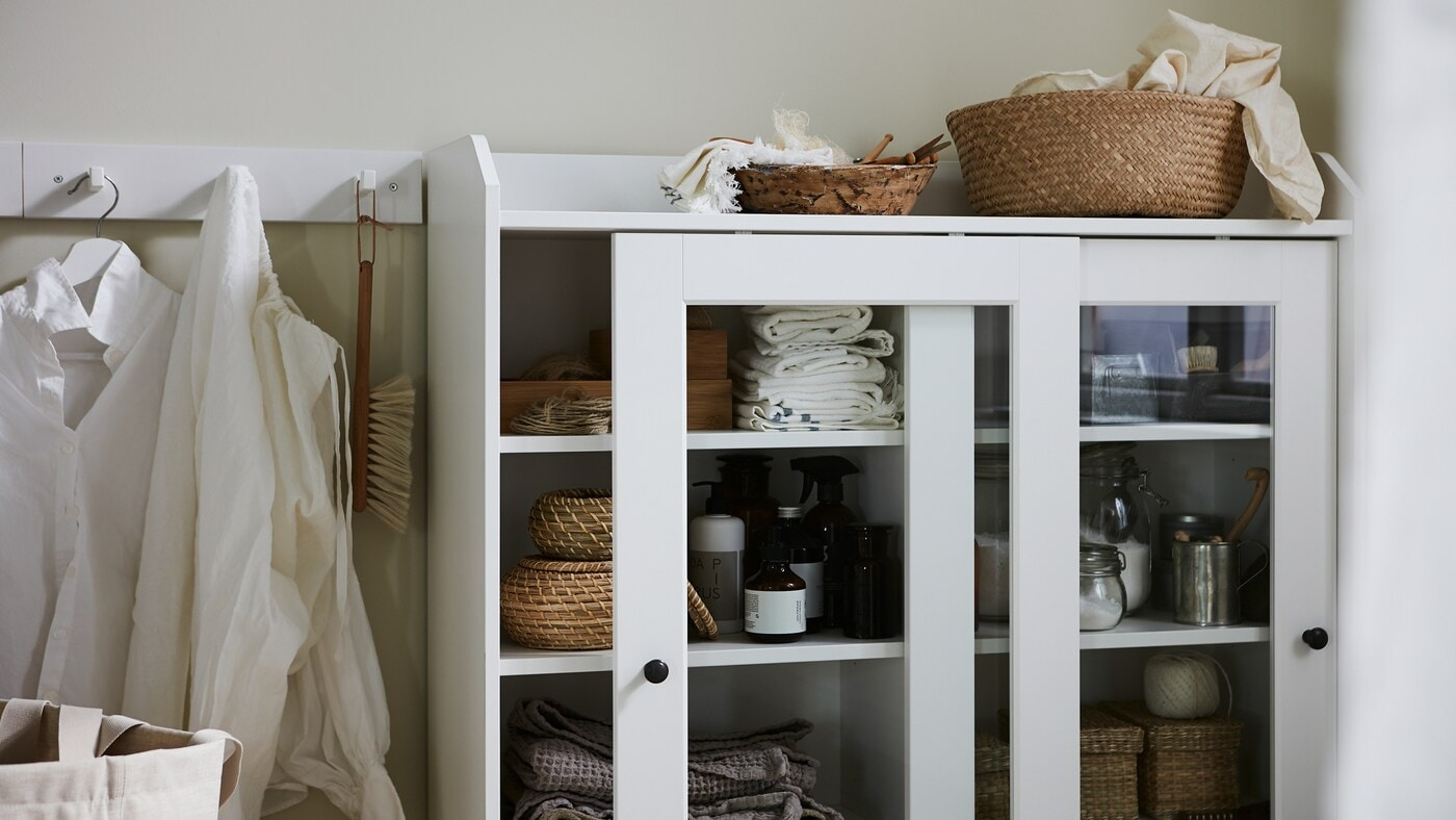 Shirts on hooks, a glass-door cabinet with boxes and a basket in natural materials, folded textiles, and laundry products.
