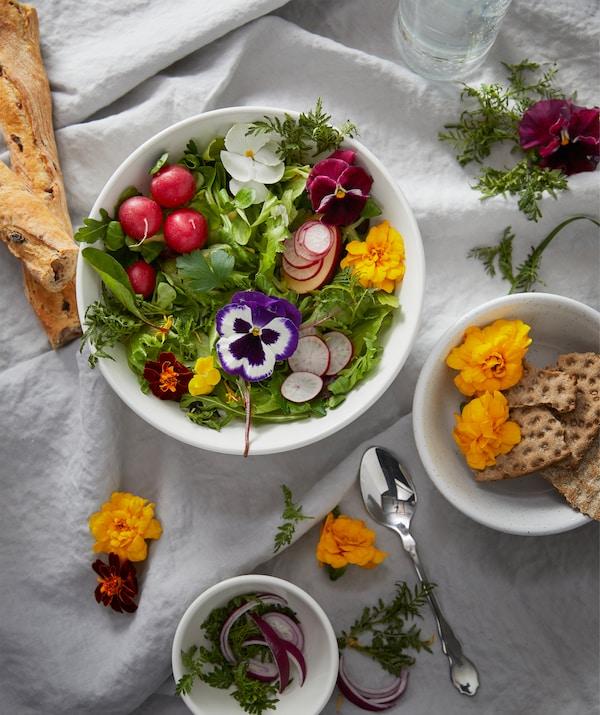 シワの入った白い布を掛け、パンや自家栽培の野菜、花が入ったサイズ違いのボウルを載せたテーブルセットの一部。