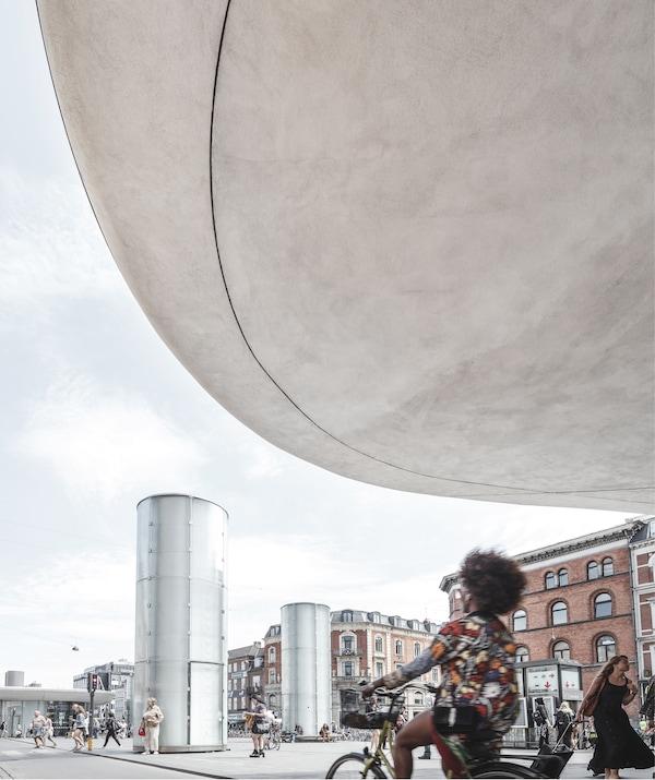 شخص يقود دراجته أسفل سقف حجري كبير في بلازا بها أعمدة معدنية.