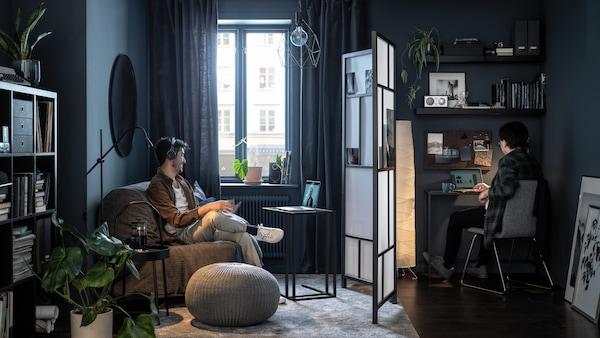 شخصانجالسان على جانبي غرفة جلوس، يفصل بينهما مقسم غرفة RISÖR، وكل منهما يركزعلى شاشته.
