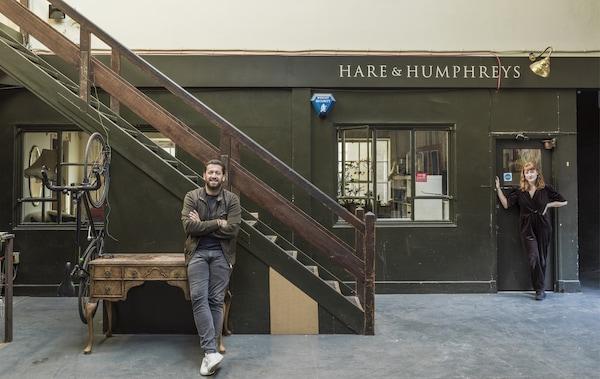 شخصان يقفان خارج متجر قديم ودرج.