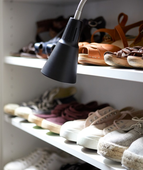 Shoes lined up on shelves with a black work lamp.