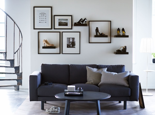 Shoes sit on shelves and in frames on a wall in this living room, making them decoration as well as footware.