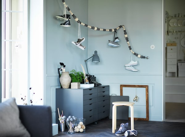Shoes stored in the corner of a bedroom by hanging them by their laces over a beaded garland.
