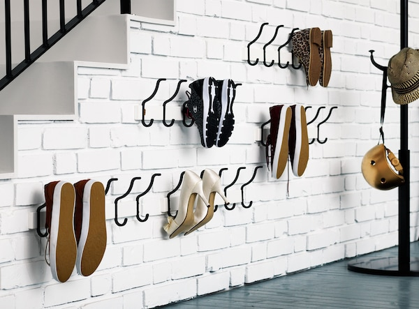 Shoes stored on black hooks mounted on a white brick wall under the stairs in this hall.