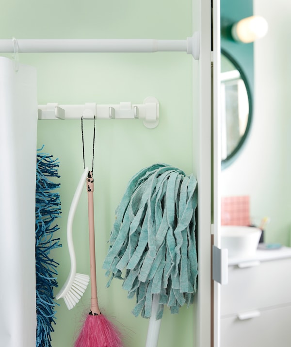 Shower curtain fitted as partition along bathroom wall, slid to the side to reveal row of cleaning equipment hanging behind.