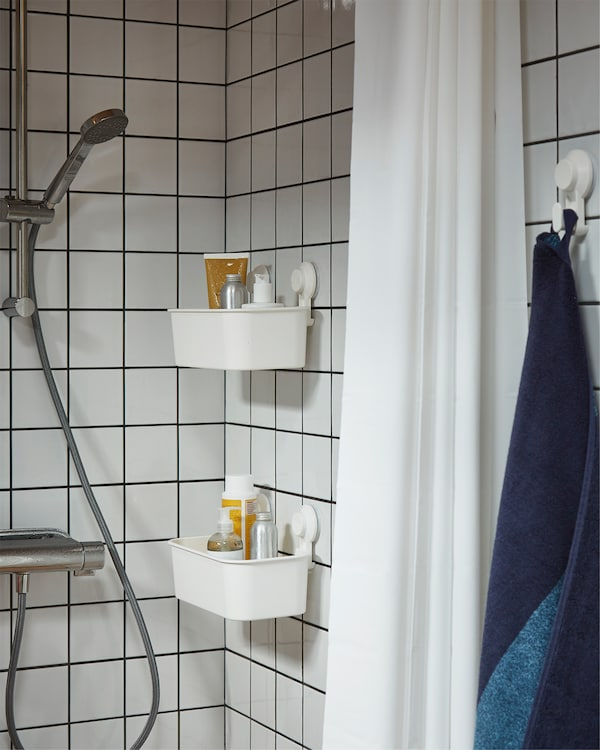 Shower in white tiles, white shower curtain and two white baskets with suction cups that store shampoos and shower gels.