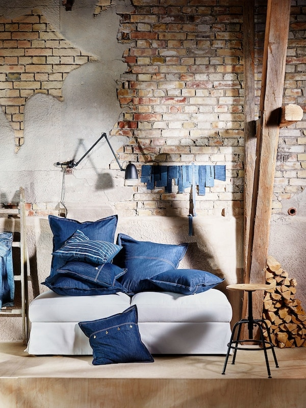 Shown piled on a sofa, square denim SISSIL cushion covers come in two sizes with details like buttons and jean-like seams.