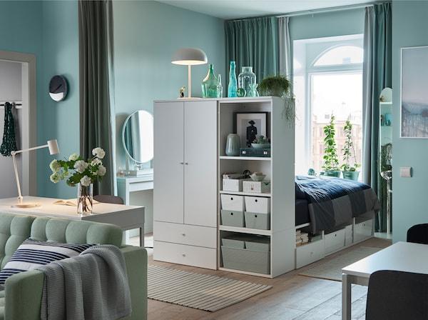 شقة بغرفة نوم واحدة باللون الأخضر الفاتح الهادىء مع ستائر خضراء وكنبة خضراء وهيكل سرير أبيض مع تخزين.