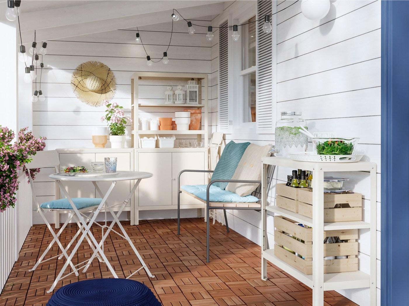 شرفة بها كنبة، وطاولة وكرسي، مع وسائد أزرق وكريم، ووحدة رفوف أبيض عاجي KOLBJÖRN من ايكيا وسلاسل إضاءة.