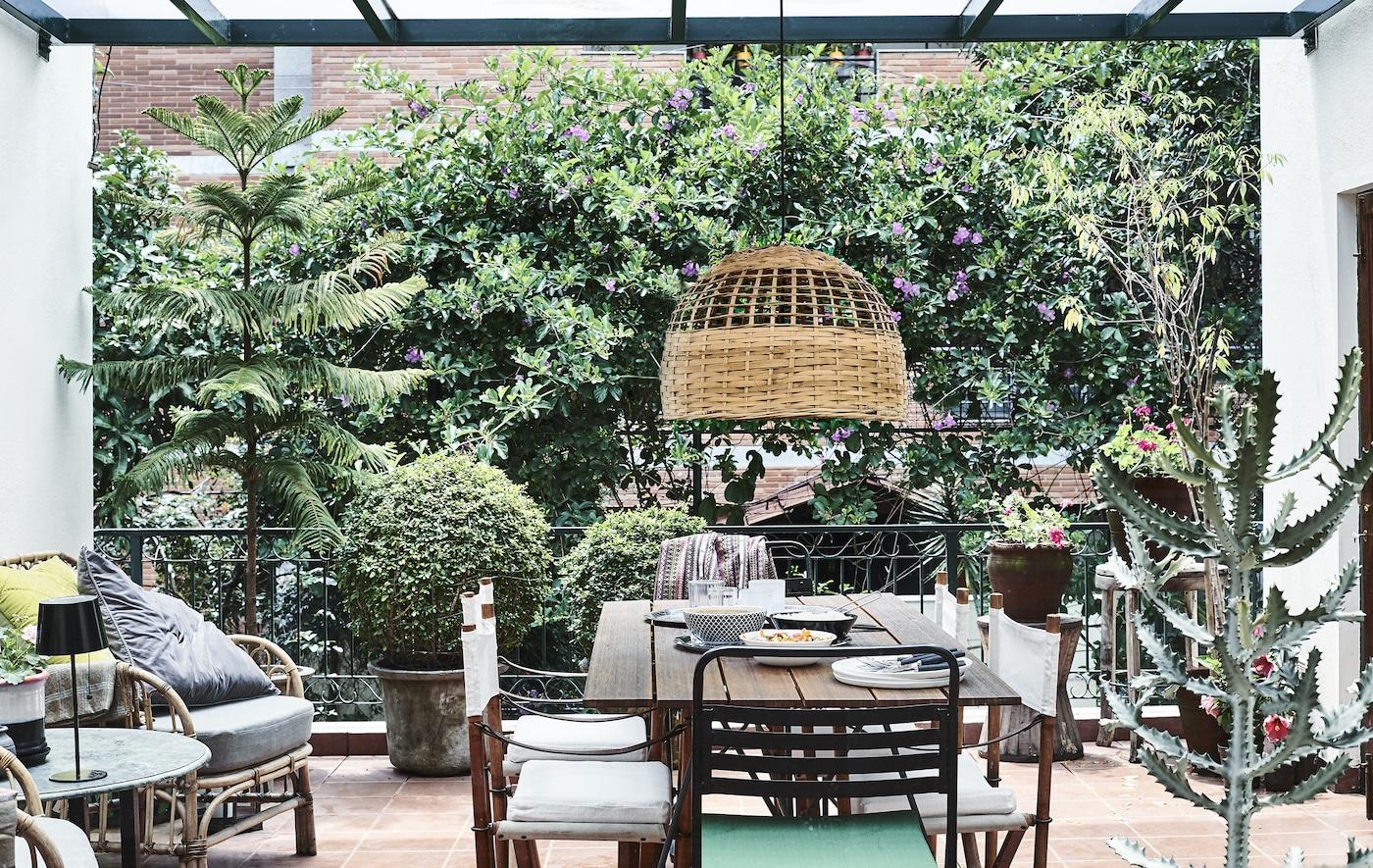 شرفة بها نباتات، وكراسي، وطاولة ومصباح معلق.