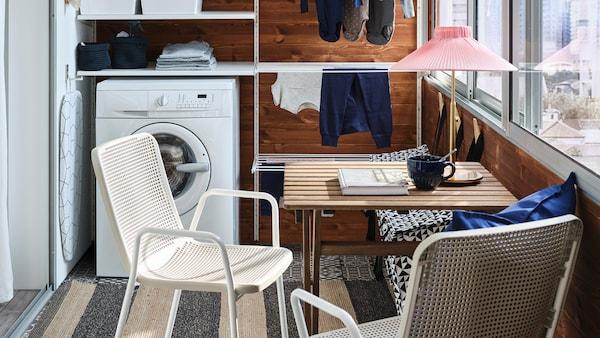شرفة صغيرة بها نظام تخزين أبيض للمغسلة،وغسالةملابس، وطاولة صغيرة وكرسيان بلون أبيض/بيج.