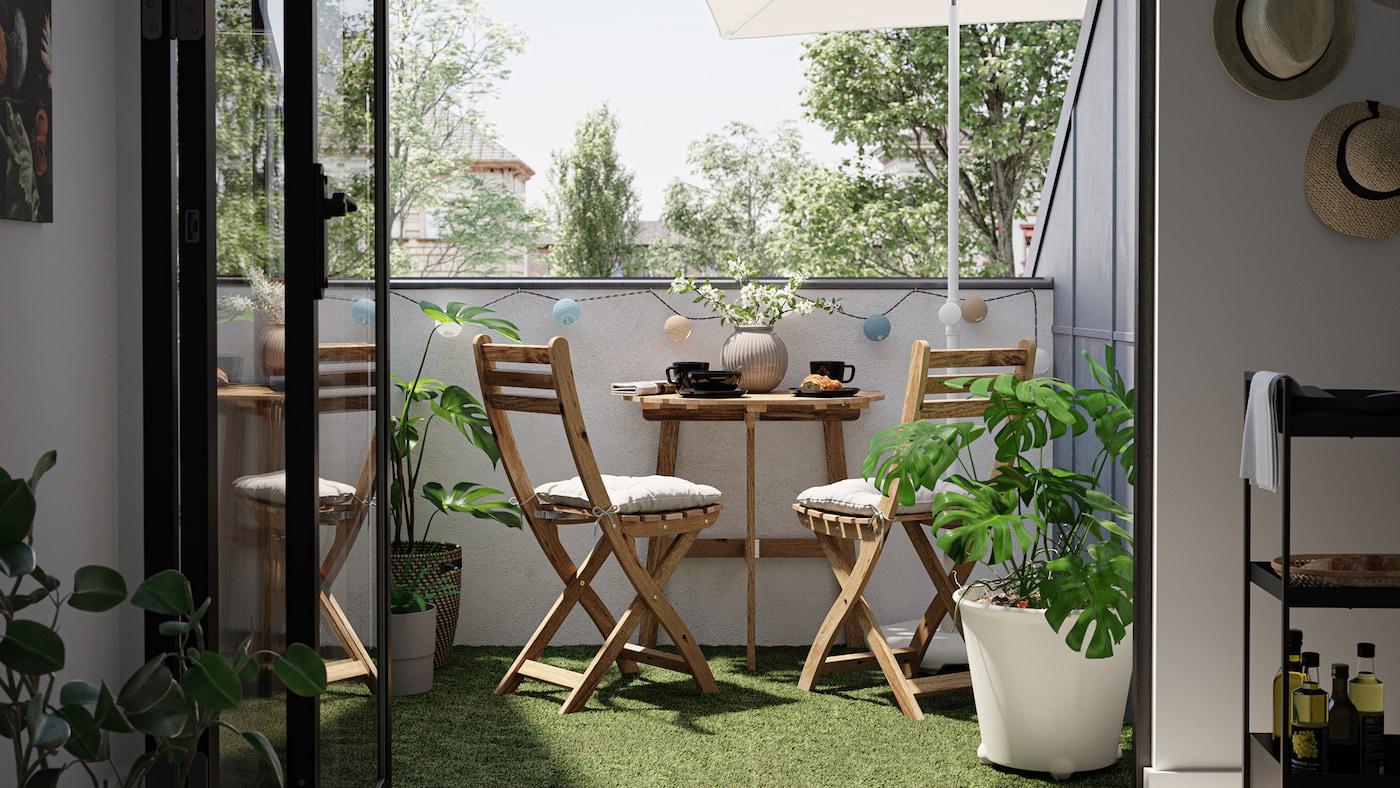 شرفة صغيرة بها طاولة وكراسي خشبية وأرضية من العشب الصناعي ونبات MONSTERA في آنية نباتات بيضاء.