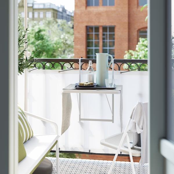 شرفة صغيرة بحاجز أبيض وحولها حواجز حماية سوداء، وكرسي وطاولة لون أبيض عليهازجاجة وترمس.