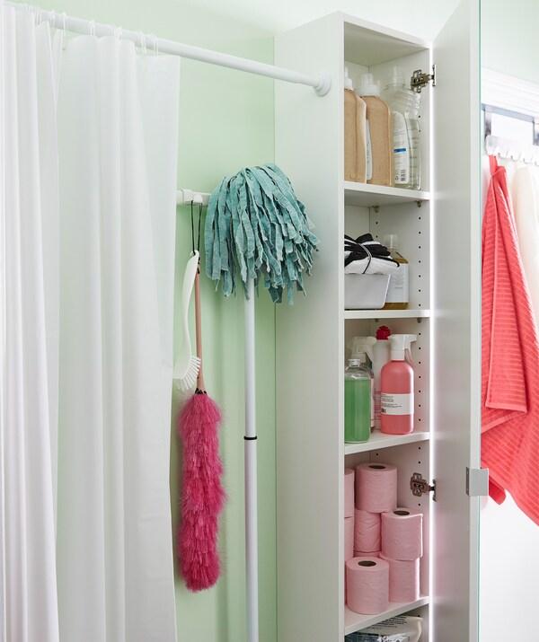 Шторка для душу створює перегородку вздовж стіни ванної кімнати. Шафа поруч наповнена різними аксесуарами для ванної кімнати.