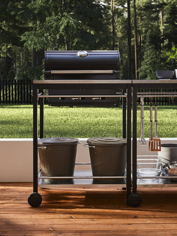 شواية فحم سوداء مع عربة من الستنلس ستيل مع أدوات مطبخ، وسلطانيات، وحاويات مع أغطية.