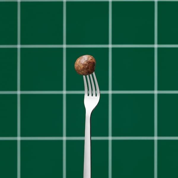 شوكة ستنلس ستيل محمولة في وضع مستقيم، وأسنانها مغروسة في كرة لحم نباتية. حائط ببلاطات خضراء في الخلفية.