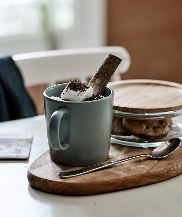 شوكولاتة ساخنة مع مارشمالو في كوب رمادي-أزرق تقدم على لوح تقطيع مع كعك في مرطبان زجاجي بغطاء من الخيزران.