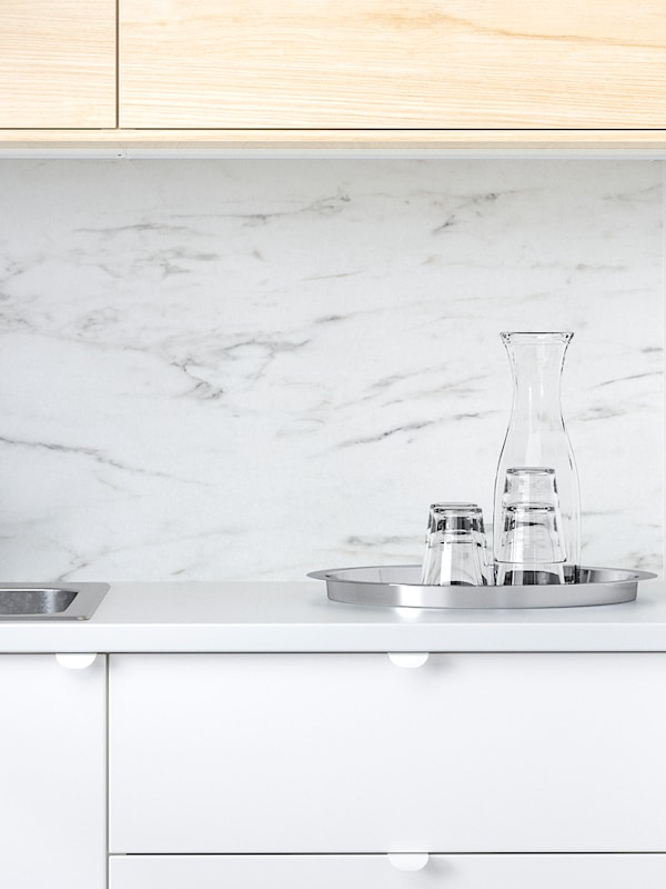 SIBBARP wall panel in white marble effect in a kitchen with fronts in white and birch, a tray with glasses and a carafe.