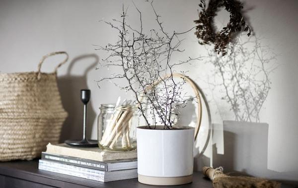 Sideboard mit einer Vielzahl von Dekorationen, u. a. mit UPPVAKTA Übertopf, in dem eine Pflanze zu sehen ist