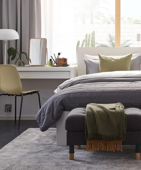 Siististi pedattu sänky jonka vieressä on valkoinen kampauspöytä. Sängyllä on erivärisiä koristetyynyjä sekä tummanvioletti päiväpeitto. Lattialla on iso vaaleanharmaa matto.