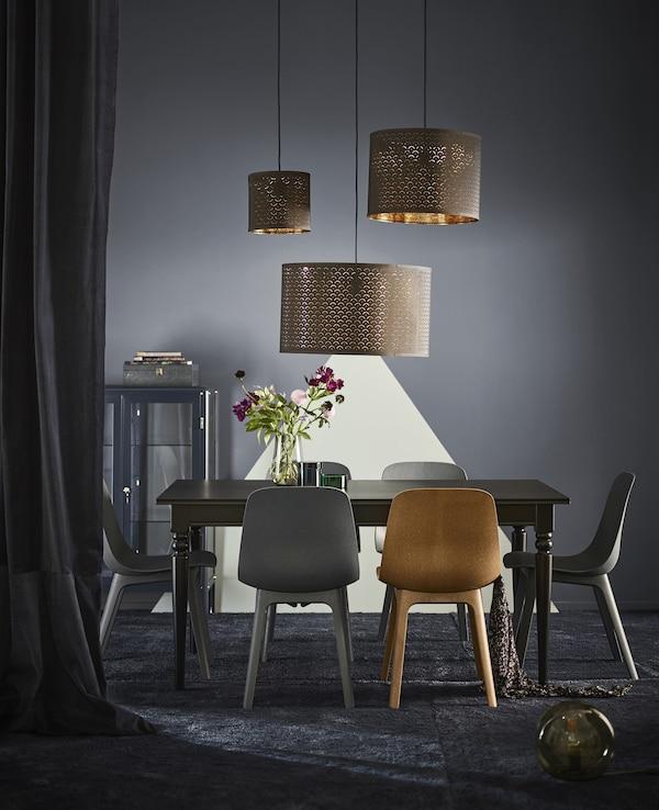 Sillas ODGER fabricadas con madera renovable y plástico reciclado colocadas alrededor de una mesa de comedor bajo tres lámparas de techo.