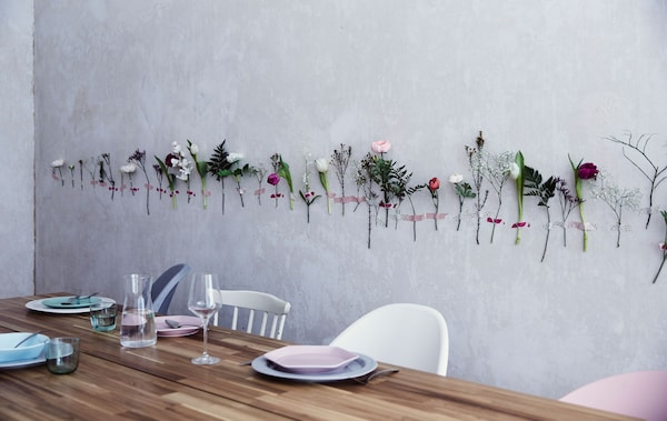 Single flower stems taped in a line along a white wall, behind a wooden dining table set with plates and cutlery.