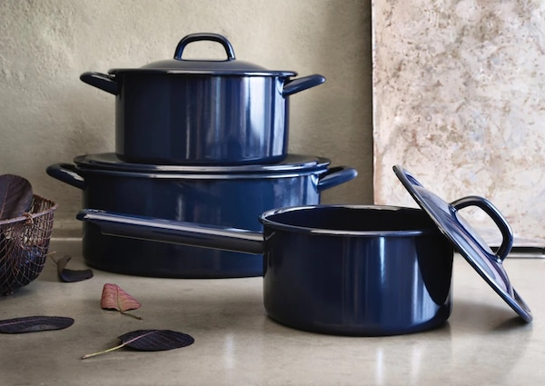 Синие эмалированные кастрюли и ковш на нейтральном фоне