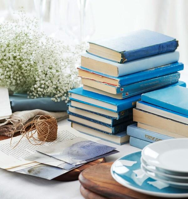 Синие книги, перекати-поле (цветы) и тарелки по центру стола для расстановки.