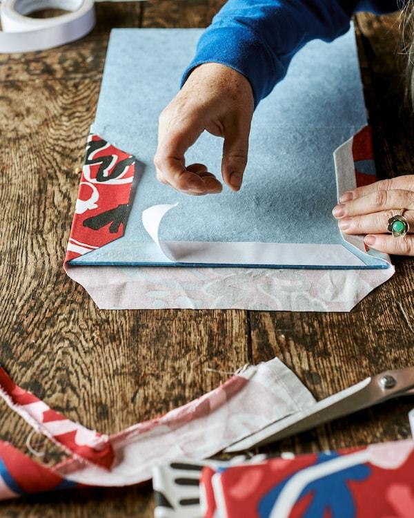 Синий блокнот открыт на первом развороте. Руки наклеивают двусторонний скотч на край страницы, чтобы закрепить красную узорчатую ткань.