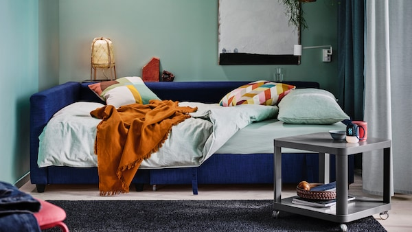 Sininen FRIHETEN- vuodesohva joka on levitetty sängyksi. Sohvan päällä vaalenvihreät BERGPALM-vuodedvaatteet, tyynyjä ja ruskea viltti.