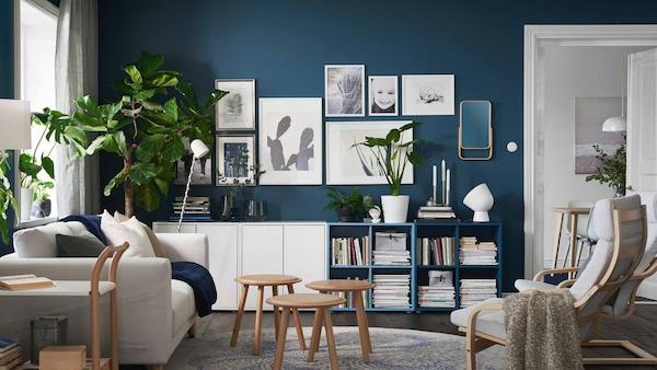 Siniseinäinen olohuone, jossa kaapisto, nojatuoli, sohva, viherkasveja ja tauluja seinällä.