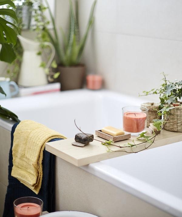 SINNLIG Duftkerze im Glas mit Pfirsich- und Orangenduft in Orange auf einem Holzbrett über einer Badewanne