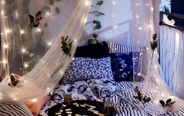 Široká posteľ na krytom balkóne so sieťou proti komárom IKEA SOLIG ozdobenou kvetmi a svetelnými reťazami LED s dominom a nápojmi na podnose.