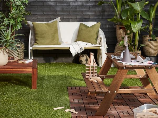 Sisäpihalla erilaisia kesäkalusteita. Maa on peitetty erilaisilla lattiaritilöillä.