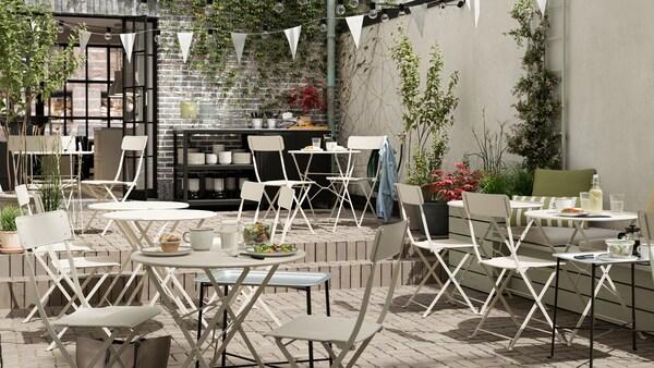 Sisäpihalle rakennettu kahvila, jossa beiget, metalliset taittotuolit ja -pöydät.
