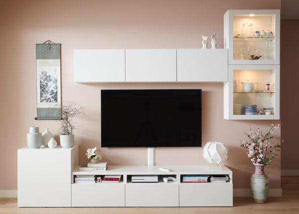 Sistema BESTÅ em branco com móvel de tv, módulos de parede e frentes brancas e de vidro