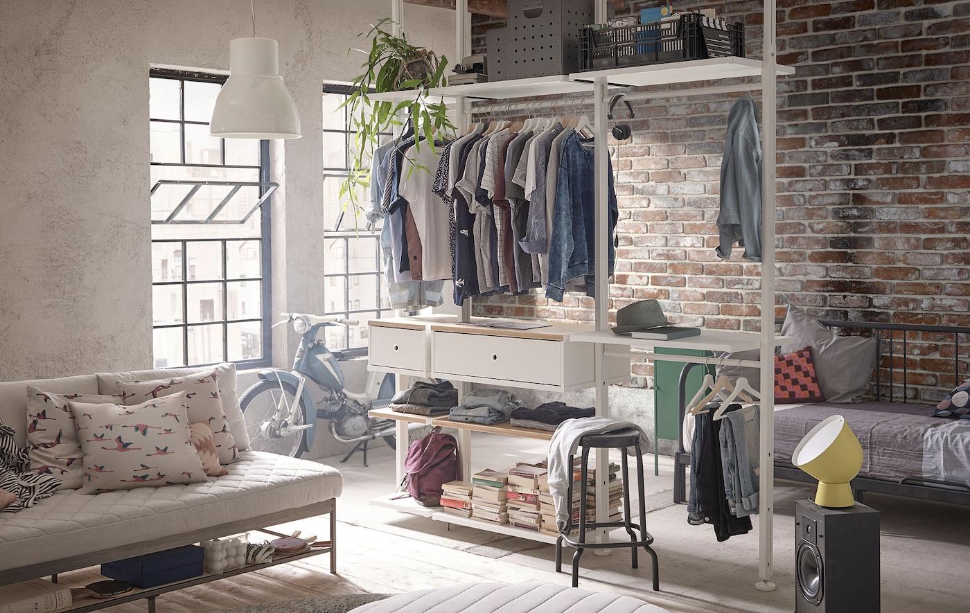 Sistemul de depozitare ELVARLI, plin cu îmbrăcăminte și cărți, într-un apartament situat la mansardă, în nuanțe delicate și cu cărămizi expuse.