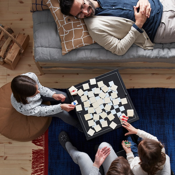Sitting and lying family members gathered around a game being played on a combined coffee table and board game.