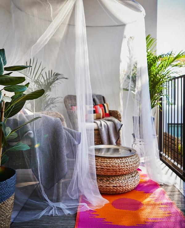 Sitzbereich mit zwei Sesseln und einem kleinen Tisch unter SOLIG Netz in Weiß.