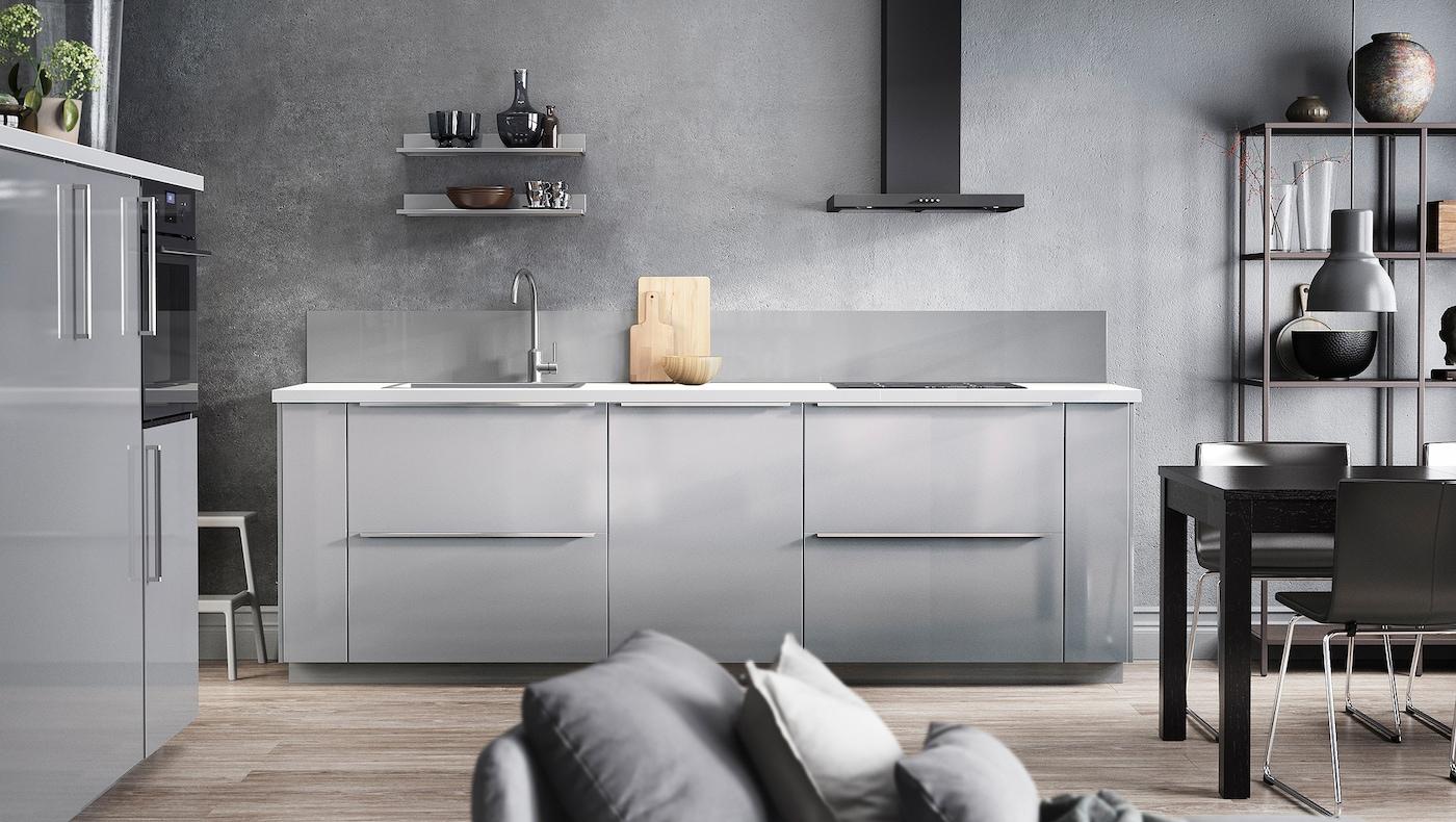 Siva kuhinja s RINGHULT frontovima fioka visokog sjaja i vratima u svetlosivoj nijansi, belom radnom pločom i crnim aspiratorom.