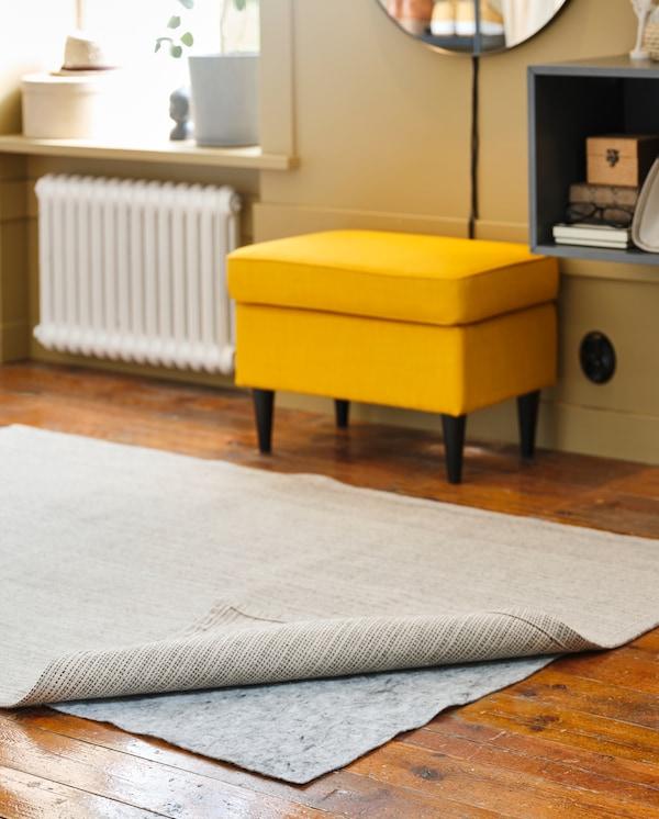 Siva podloga za tepih nalazi se ispod prirodnog tepiha/ tepiha prljavobele boje. Žuta stoličica i tamnosivi zidni ormarić su u pozadini.