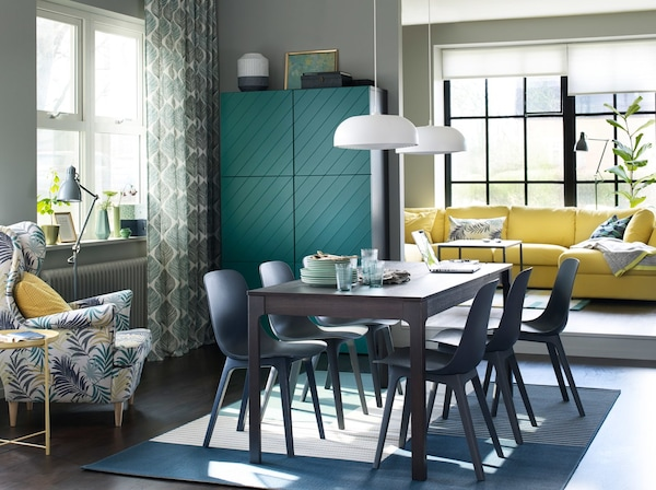 Six blue ODGER chairs around an EKEDALEN extendable table in a dining room, with a yellow sofa in the background.