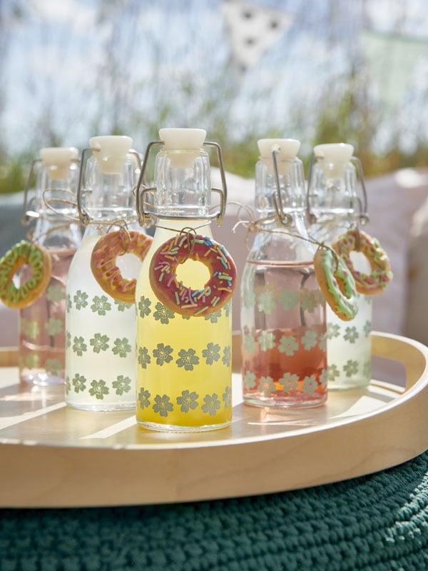 Six bouteilles KORKEN à motifs remplies de boissons aux couleurs variées.